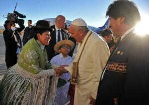 epa04837903 A handout picture made available by the Bolivian Information Agency (ABI) shows Pope Francis (C) being welcomed by members of the local community as Bolivian President Evo Morales (R) looks on, upon his arrival at El Alto Airport in El Alto, Bolivia, 08 July 2015. Pope Francis is in Bolivia as part of his Latin American tour from 05 to 12 July 2015.  EPA/BOLIVIAN INFORMATION AGENCY  HANDOUT EDITORIAL USE ONLY/NO SALES