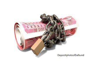A rolled up british one hundred pound note wrapped with chains and secured with a padlock on an isolated background