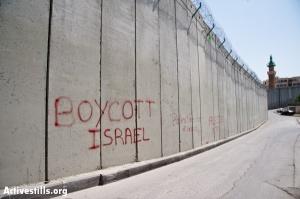 "EAST JERUSALEM, OCCUPIED PALESTINIAN TERRITORIES - MARCH 26: Graffiti on the Israeli separation barrier dividing the East Jerusalem neighborhood of Abu Dis reads, ""Boycott Israel""."
