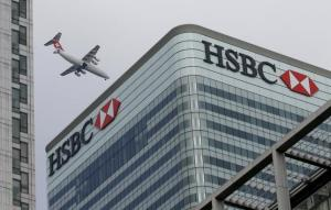 A Swiss International aircraft flies past the HSBC headquarters building in the Canary Wharf financial district in east London in this February 15, 2015 photo. REUTERS/Peter Nicholls/Files